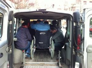 Mikrobusz hátsó részébe egy kerekesszékes embert rögzítenek